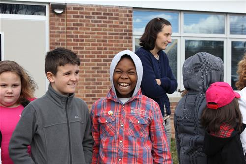 Students smile outside a KCSD school building.